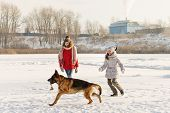 Joyful Teens Spend Time Together With Lovely Pet German Shepherd Dog On Walk In Winter Park On Sunny poster