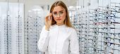 Happy Female Optometrist, Optician Is Standing With Many Glasses In Background In Optical Shop. Stan poster
