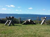 Sawing Logs On A Wooden Stand On A Green Lawn. Ocean View. Supports For Cutting Firewood And Pile Of poster