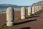 picture of bollard  - A set of concrete precast parking bollards stretch into the distance with a path pebble beach and the sea in the distance - JPG
