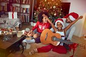 Happy family celebrating Christmas together and  playing guitar songs.  poster