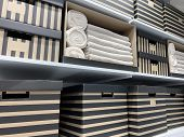 Rows Of Stacked Storage Carton Boxes And Home Textyle Stacked On Shelves. poster