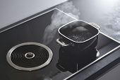 Modern Electric Induction Cooker With Built-in Ventilation And Extractor Hood Which Draws Steam From poster