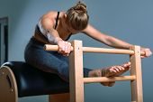 Beautiful Positive Blond Woman Is Being Prepared Performing Pilates Exercise, Training On Barrel Equ poster