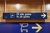 Direction signs inside a large airport, way to the gates, also written in Danish, To all gates poster