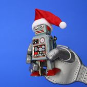 The Robot Holds A Small Retro Robot In His Hand. The Robot Has A Santa Hat. Christmas And New Year C poster
