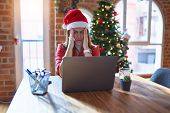 Beautiful woman sitting at the table working with laptop wearing santa claus hat at christmas suffer poster