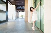 Graceful Young Ballerina Practicing Dance On Tiptoe Outdoors poster