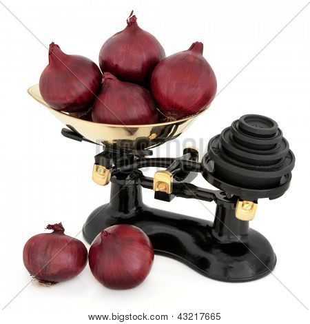 Red onions and retro kitchen scales with cast iron imperial weights over white background.