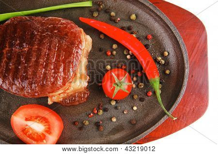 main entree : platter of roasted beef steak served with hot cayenne peppers cherry tomato green chives on metal pan isolated over white background