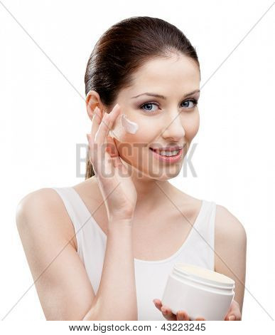 Woman applying moisture cream from container on face, isolated on white. The pursuit of beauty