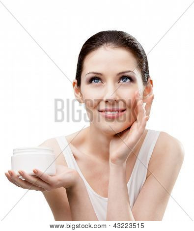 Woman putting on moisture cream from container on face, isolated on white. The pursuit of beauty
