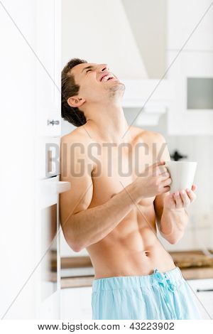 Half-naked man keeping cup of coffee stands at kitchen leaning on the refrigerator
