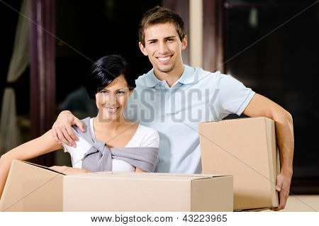 Happy couple carrying cardboard packages while moving to new house