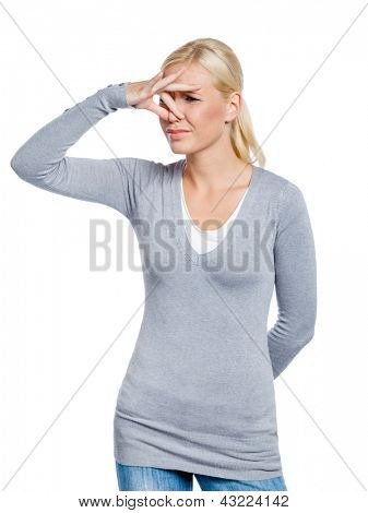 Girl covers nose with hand showing that something stinks, isolated on white