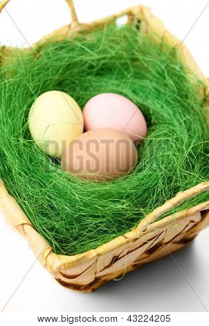 Multicolored easter eggs are in wattled basket with sisal green fibre, isolated on white