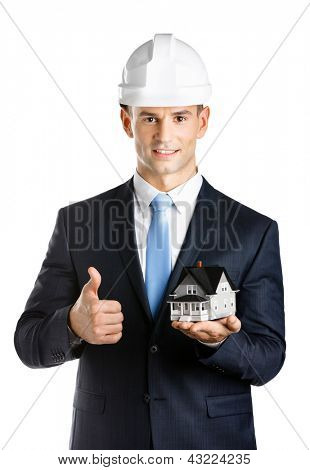 Engineer in white hard hat shows small model house and thumbs up, isolated on white