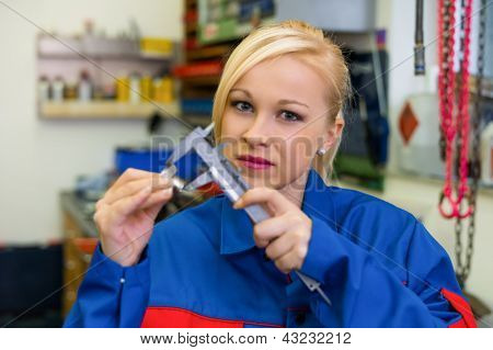 an apprentice (apprentice) in the metal industry. measure a workpiece in the workshop. rare female occupations