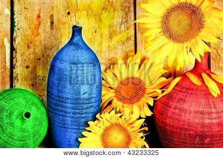 Vintage image of sunflowers and pottery with  a rustic wood planks background