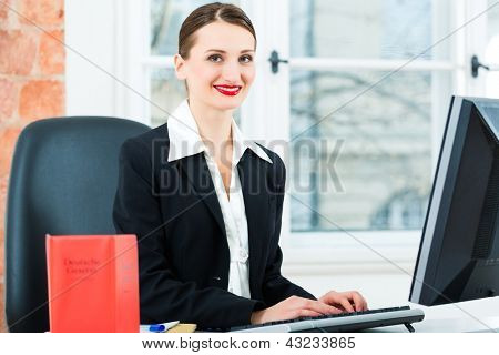 Young lawyer working in her Office, she is sitting behind folders writing into a file