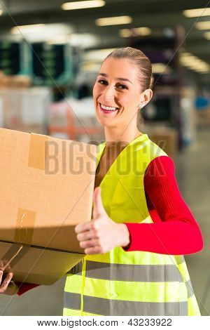 female worker with protective vest holds package, standing at warehouse of freight forwarding company