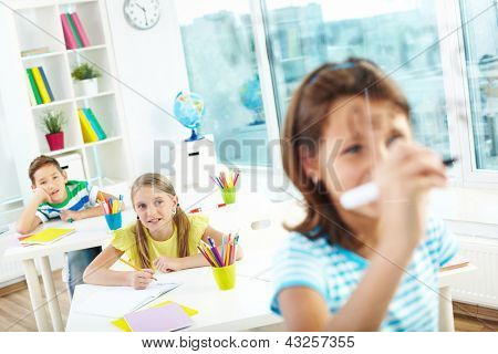 Schoolgirl doing sums on transparent board with two schoolmates looking at her
