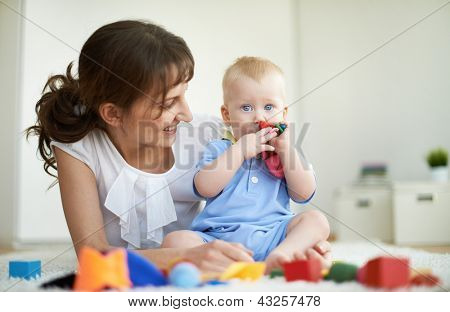 Portrait of happy woman looking at her small son during play