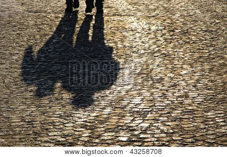 Silhouette And Shadows Of People Walking On Brick Pavement