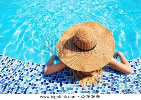 Woman In A Hat Enjoying A Swimming Pool