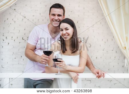 ?appy Couple Enjoying A Glasses Of Red Wine Indoors