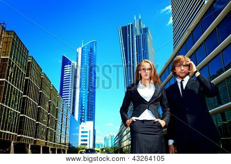 Business woman and business man is talking on mobile phone in front of skyscrapers.