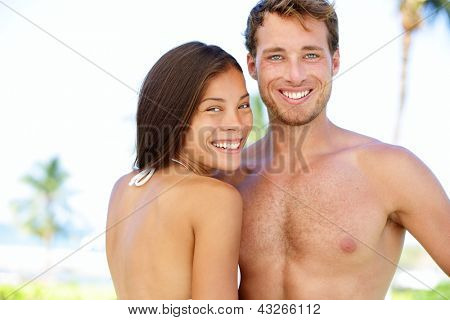 Couple beach - young multicultural people. Happy young interracial couple smiling happy looking at camera. Young asian woman and Caucasian man during summer holidays vacation under the sun.