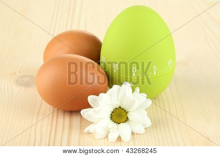 Green egg timer and eggs, on wooden background