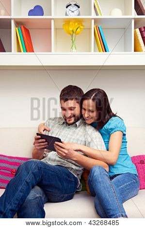 smiley young couple sitting on sofa and looking at the tablet pc