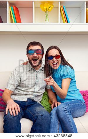 joyous couple in 3d glasses watching comedy and laughing