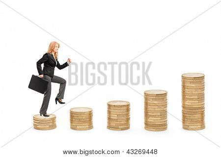 Full length portrait of a businesswoman with a briefcase walking over piles of coins isolated against white background