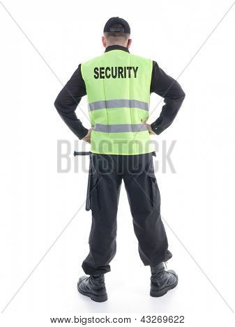 Security man wearing black uniform and yellow reflective vest standing confidently with arms resting on hips, facing back to the camera, shot on white