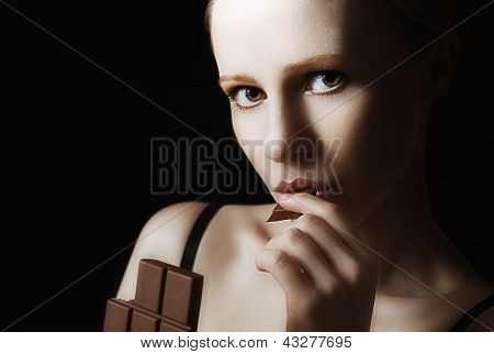 Sexy Beautiful Young Woman Eating Chocolate On A Dark