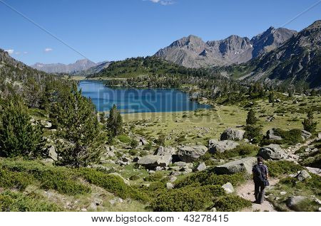 Hiker Descending To The Mountainous Lake