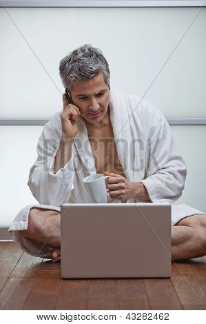 Man Wearing Bathrobe And Talking On A Mobile Phone