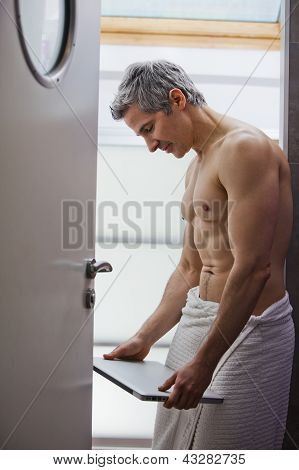 Man Wrapped In Towel And Holding A Laptop