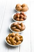 various nuts in ceramic bowls on woden table