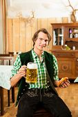 stock photo of stein  - Young man in traditional Bavarian Tracht in restaurant or pub with beer and steins and pretzel - JPG