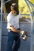 pic of air paint gun  - Construction steel worker uses a paint sprayer to apply a primer coat to metalwork - JPG