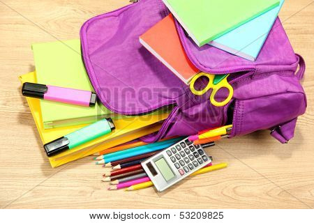 Purple backpack with school supplies on wooden background