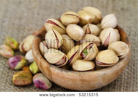 Pistachio nuts with and without shell in wooden bowl, close up