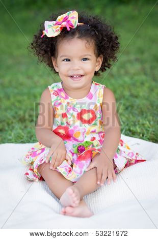 Hispanic toddler with an afro hairstyle sitting on the park