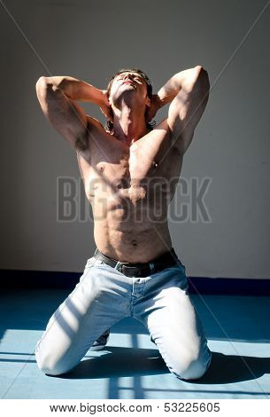 Attractive Muscleman Kneeling Shirtless With Hands Behind Head, Looking Up