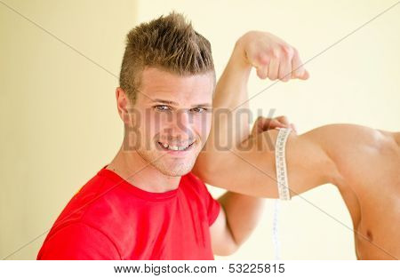 Personal Trainer Measuring Client Bicep With Tape Meter