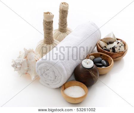 spa still life with spa herbal balls, candlestick, stones and salt in wooden bowl over white